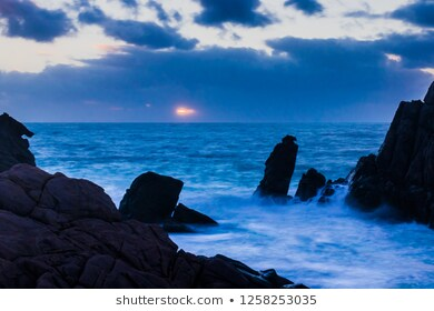 jagged-rocks-on-shoreline-dusk-260nw-1258253035
